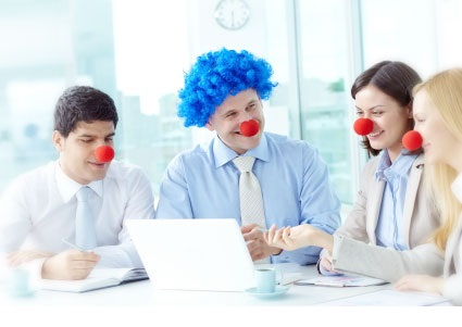 four business attired people with clown noses on their noses